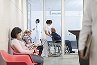 Nurse pushing patient in wheelchair at waiting area - ZEF005933