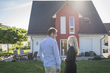 Estate agent and customer standing in front of one-family house - PAF001436
