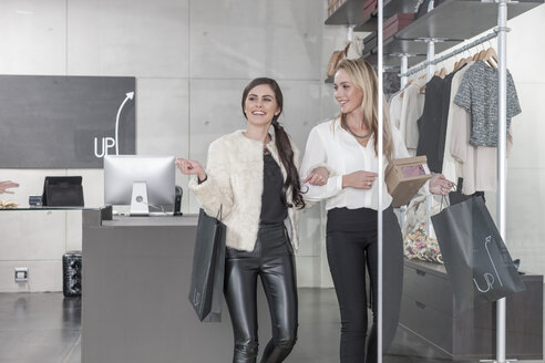 Two happy women shopping for clothes - ZEF006691