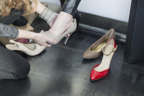 Shop assistant helping woman trying on new shoes - ZEF006703
