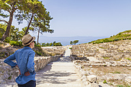 Greece, Rhodes, Kamiros, young man looking to ruin site - WD003148