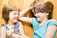 Two laughing sisters lying on wooden floor - LVF003517