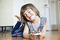 Smiling little girl lying on wooden floor with smartphone - LVF003525