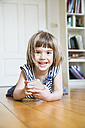 Portrait of happy little girl lying on wooden floor with smartphone - LVF003527
