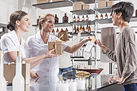 Shop assistants in wellness shop handing over gift box to client - ZEF006516