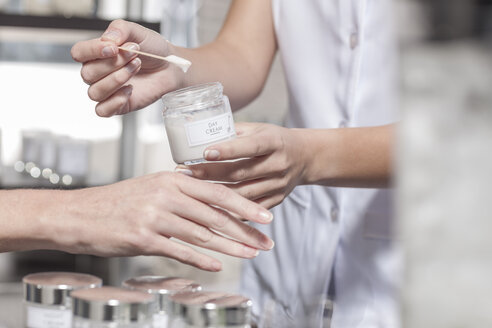 Cosmetician applying day cream on client's hand - ZEF006460