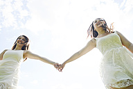 Two happy young women hand in hand - BFRF001263