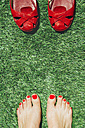 Barefoot women with nails painted red next to a pair of red shoes, on the green grass - GEMF000248