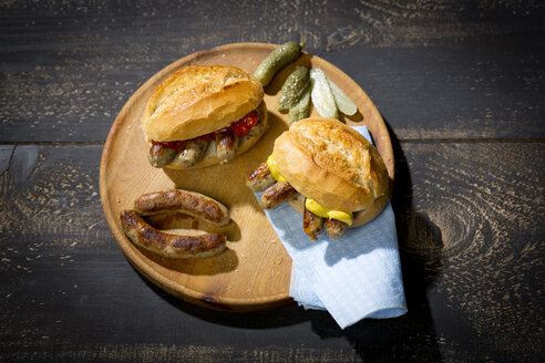 Nuremberg grilled sausage, wheat roll with mustard ketchup and gherkin on wooden plate - MAEF010766