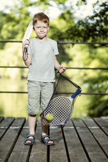 Portrait of little boy holding tennis racket and a bag - TAM000110