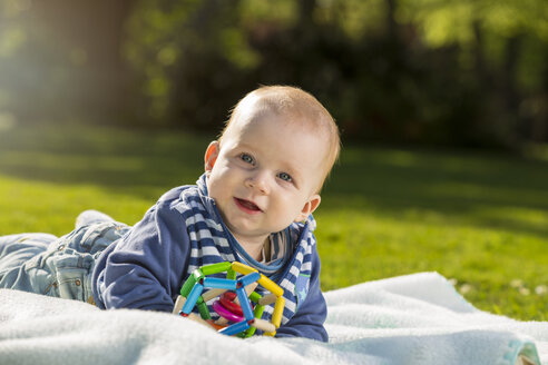 Portrait of smiling baby boy lying on blanket on a meadow - TAM000137