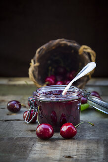 Jar of cherry jam and cherries on wood - LVF003543