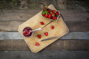 Glass of homemade strawberry jam and box of strawberries on wood - LVF003552