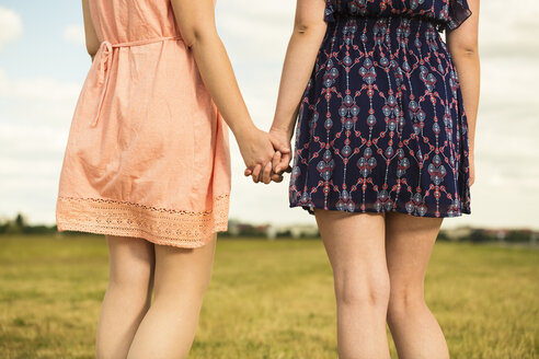 Two young women walking hand in hand, close-up - TAM000154