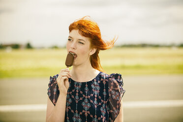 Portrait of young woman with ice lolly - TAM000118