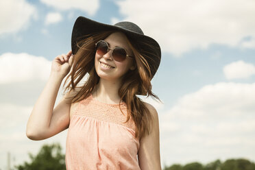 Portrait of young woman wearing hat and sunglasses - TAM000120