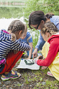 Germany, Children learning how to use compass and map - MJF001550