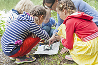 Germany, Children learning how to use compass and map - MJF001570