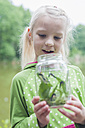 Germany, Girl holding glass with caterpillar of peacock butterfly - MJF001555