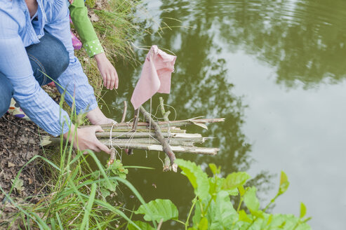 Germany, Woman putting toy raft in water - MJF001567