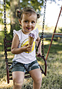 Portrait of happy little girl sitting on a swing eating ice cream - MGOF000306