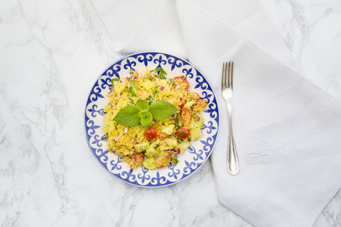 Plate of couscous salad, cloth and fork on white marble - LVF003598