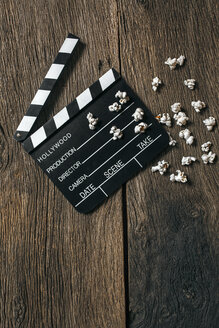 Movie clapper and popcorn on aged wood - MGOF000309