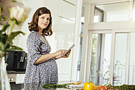 Portrait of pregnant woman with digital tablet in the kitchen - MFF001768