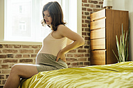 Pregnant woman  sitting on bed holding her back in pain - MFF001770