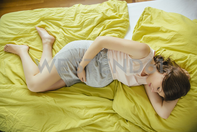 Pregnant woman sleeping on bed at home during the day - MFF001774