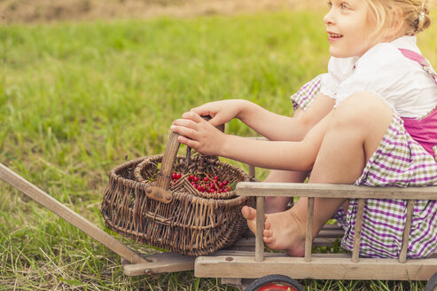 Little girl with wickerbasket sitting on a trolley - MJF001593