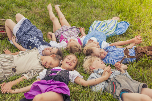 Germany, Saxony, group of children wearing traditional clothes lying on a meadow in circle - MJF001597