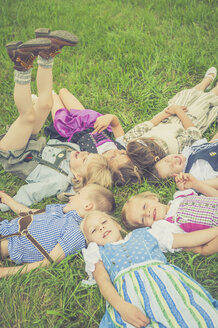 Germany, Saxony, group of children wearing traditional clothes lying on a meadow in circle - MJF001598
