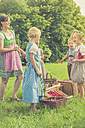 Germany, Saxony, children and their educator in traditonal clothes on a meadow - MJF001605