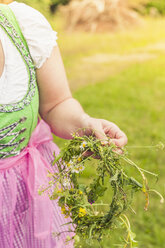 Germany, Saxony, woman wearing dirndl holding floral wreath, close-up - MJF001606