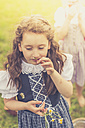 Germany, Saxony, portrait of girl wearing dirndl smelling chamomile flower - MJF001623