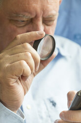 Senior man reading text on a cell phone with a magnifying glass - TAMF000124