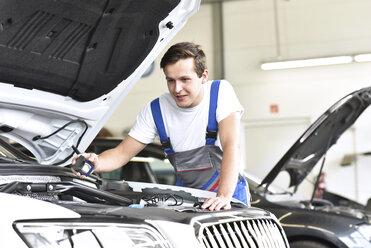 Mechanic examining engine of a car in a garage - LYF000429