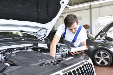 Mechanic examining engine of a car in a garage - LYF000443