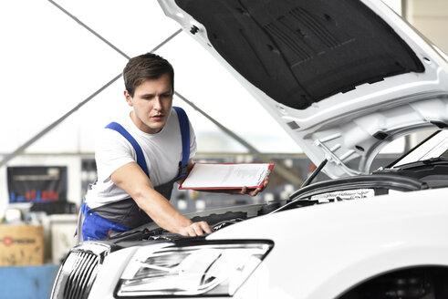 Mechanic examining engine of a car in a garage - LYF000432