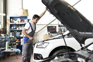 Mechanic examining engine of a car in a garage - LYF000433