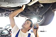Mechanic examining underbody of a car in a garage - LYF000434