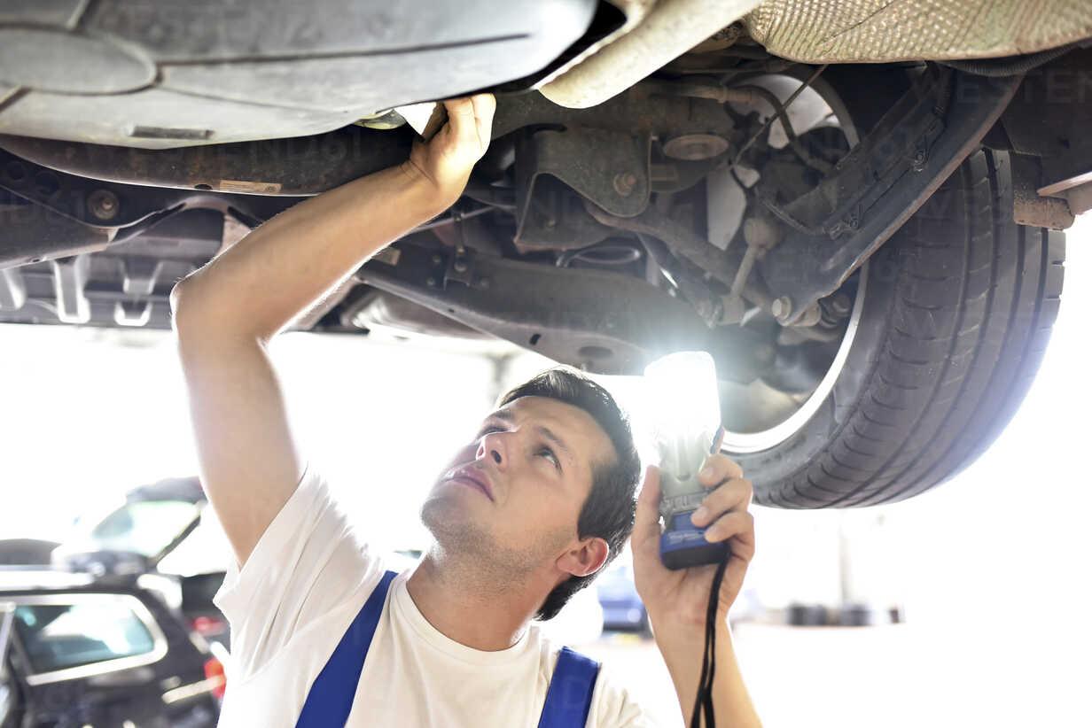 Mechanic examining underbody of a car in a garage - LYF000434 - lyzs/Westend61
