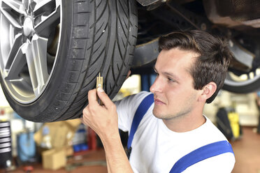 Mechanic measuring tire pattern of a car in a garage - LYF000449