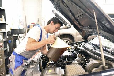 Car mechanic refilling engine oil - LYF000437
