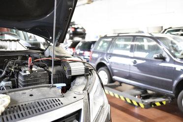 Car with open bonnet in garage - LYF000439