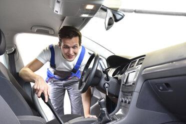 Man hoovering car interior - LYF000450