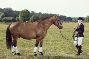Woman wearing riding gear face to face with horse on a meadow - TAM000240