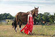 Portrait of young woman wearing red evening dress standing beside a horse on a meadow - TAMF000243