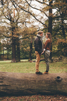 Young couple in love holding hands on a tree trunk in an autumnal park - CHAF000203